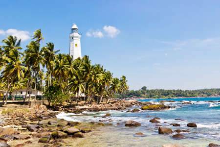 Beautiful tropical landscape with white Dondra Head Lighthouse and palms. Southern point of Sri Lanka coastline, Ceylon. Horizontal image