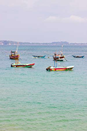 pristine corals: Fishing boats in beautiful ocean near coastline of Sri Lanka, Ceylon. Vertical image Stock Photo