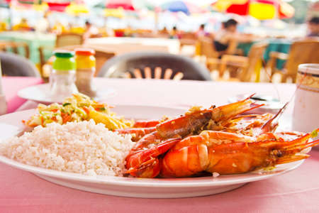Grilled shrimps with rice and vegetable salad. Delicious healthy eating photo