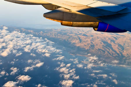 going places: Sea and rocky coastline. View under wing of airplane Stock Photo