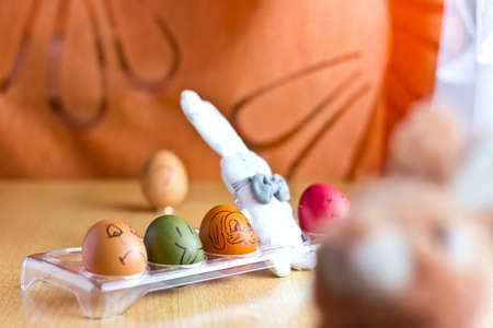 ring stand: Colored eggs and easter bunny on stand. Selective focus on eggs. Multicolored blurred background with easter bunny at foreground and question egg on wedding ring at background Stock Photo