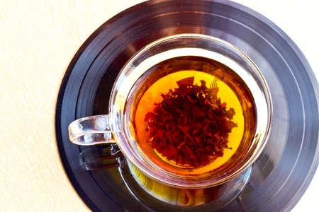 tea mug: Strong black tea in glass cup on vinyl record disc