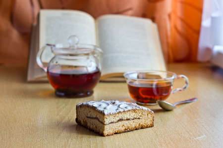 Still life composition: morning tea in glass cup and teapot with sweet cake and reading book.Selective focus and blurred background photo