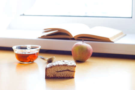 composition book: Still life composition: book tea apple cake. With selective focus and blurred background. Sunlight from window