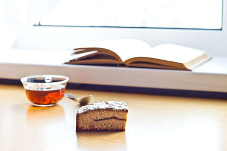 composition book: Still life composition: book tea cake. With selective focus and blurred background. Sunlight from window Stock Photo