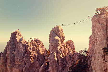 chasm: People crossing the chasm on the hanging bridge. Black sea background, Crimea, Russia. Vintage image