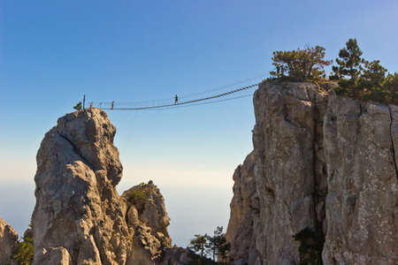 People crossing the chasm on the hanging bridge. Black sea background, Crimea, Russia Imagens
