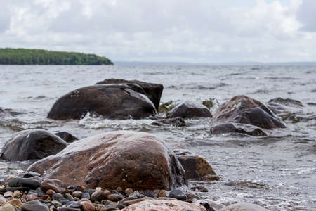 onega: Landscape of Onega lake shore. Stones in water. Rain is coming Stock Photo