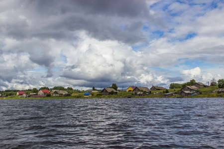 onega: Landscape of Onega lake with small village on lake shore. View from the boat. Karelia, Russia Stock Photo