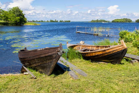 lake shore: Summer rural landscape of lake shore with old wooden fishing boats
