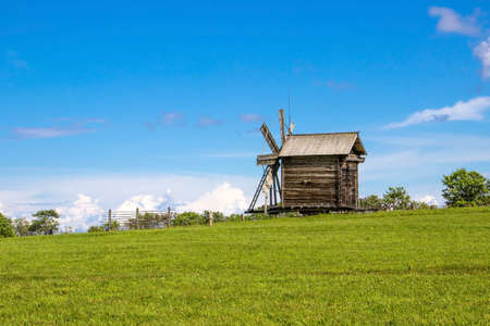 Rural landscape. Traditional wooden windmill on green hill. Kizhi Island.