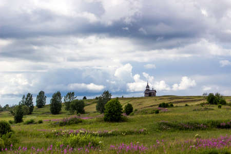 Traditional wooden chapel on hill. Summer landscape with cloudy sky. Kizhi Island, Russia