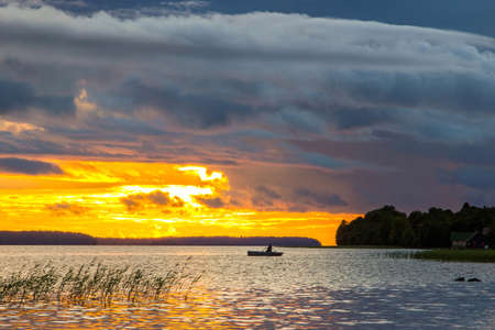 Lonely fishing boat on Onegs lake with beautiful sunset background