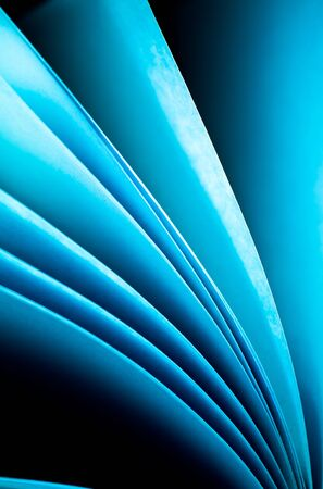 arise: Blue notepad paper illuminated by LED viewed in portrait arise from lower right Stock Photo