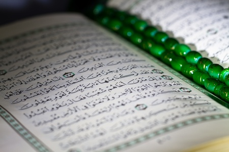 opened holy quran with green rosary beads Stock Photo