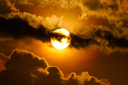 serene: the morning tropical sun seen behind the clouds