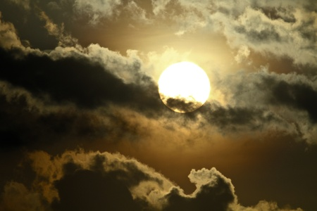 the sun with silver rays behind the clouds Stock Photo