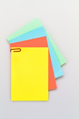 assignment: colorful notepad arrangement on white background with yellow paper on top