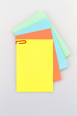 looseleaf: Colorful notepad arrangement on white background with green paper at the back