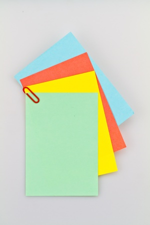 looseleaf: Colorful notepad arrangement on white background with green paper on top