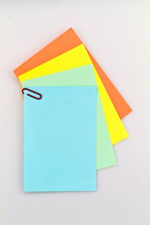 assign: Colorful notepad arrangement on white background with blue paper on top