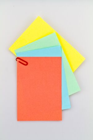 looseleaf: Colorful notepad arrangement on white background with red paper on top