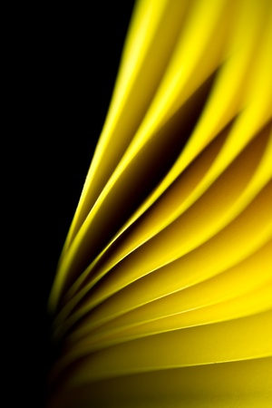 Yellow A4 paper illuminated by LED lights and twisted with black background