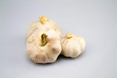 Three garlic bulbs isolated over a white bluish background in landscape orientation photo
