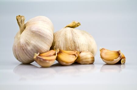 two garlic bulbs with peeled off cloves on white bluish photo