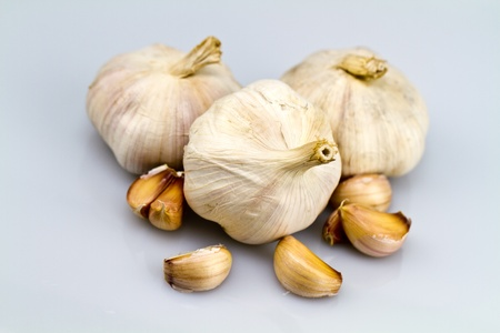 peeled off: three garlic bulbs with peeled off cloves on white bluish background