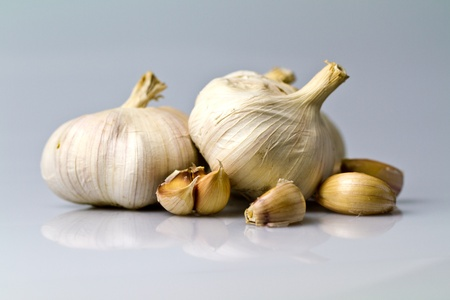 Three garlic bulbs with peeled off cloves on white bluish background one hidden photo