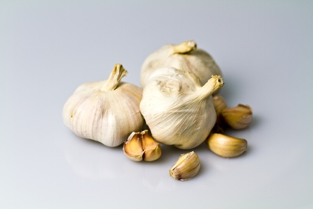 three garlic bulbs with peeled off cloves on white bluish background view from above photo