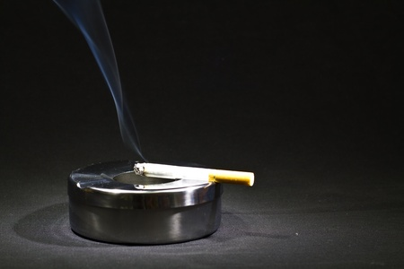 a cigarette burns on a metal ashtray with black background photo