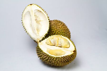 opened durian with one unopened durian on whitish surface photo