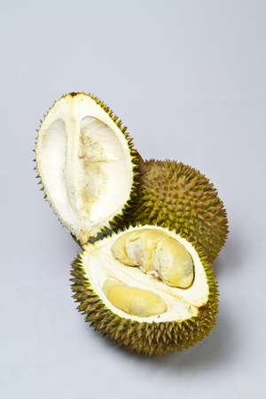 one opened durian with one unopened durian on whitish surface in portrait orientation photo