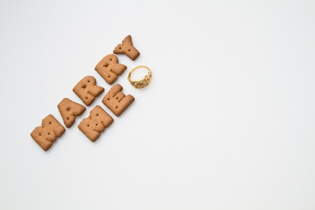 Word marry me arranged by brown biscuits with gold  ring on white background Stock Photo