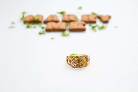 Gold ring with the words Marry Me in background on white surface photo