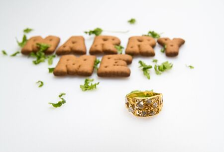 Marry me wording by brown biscuits with green leaves and gold\ ring on white surface in landscape orientation