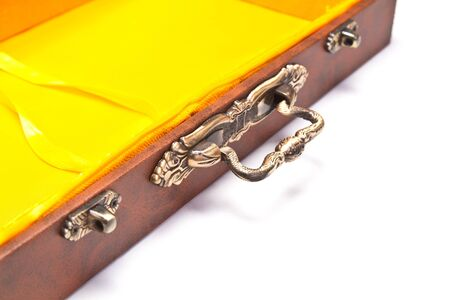 empty box with yellow inner lining on white surface with detail on handle and locks photo