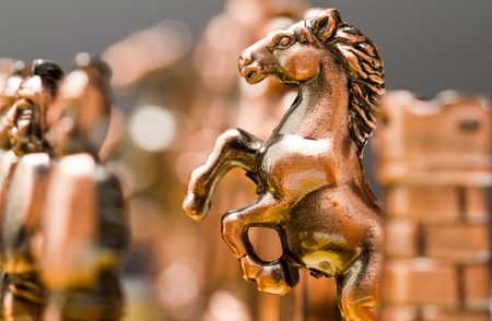 A knight piece of brass chess set behind the rook Stock Photo