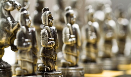 Silver chess pieces on a checkerboard blurry background photo