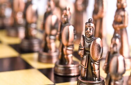 Brass chess piece in focus with other blurred pieces image in background Stock Photo