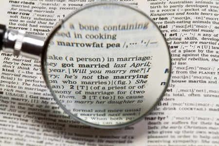 phrase will you marry me in the dictionary magnified by hand magnifying glass photo