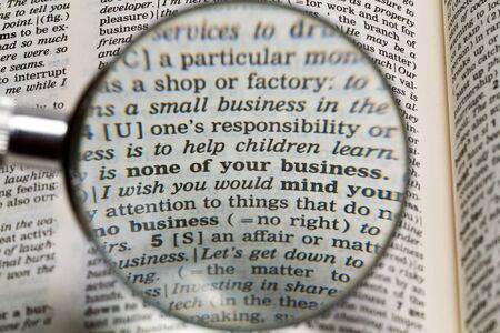 the phrase none of your business in dictionary magnified by handheld magnifying glass photo