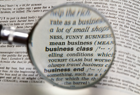 the word business class in dictionary magnified by handheld magnifying glass