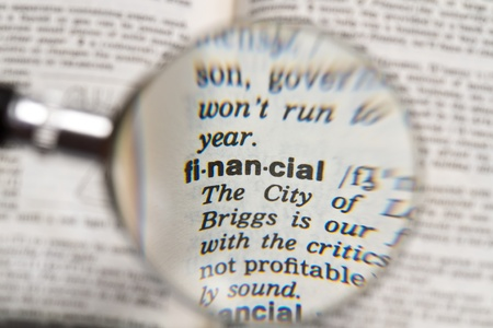 the word financial in dictionary magnified by handheld magnifying glass photo