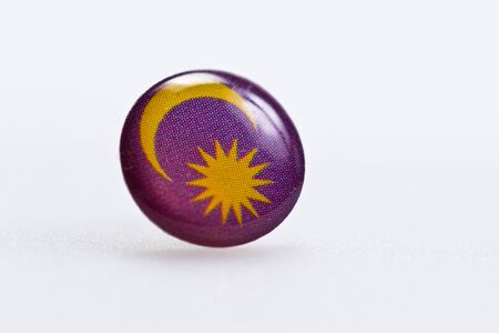 Malaysian flag symbl on thumbtack on white surface photo