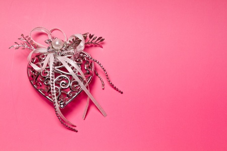Silver metal heart on pinkish background for valentive use Stock Photo - 11827229