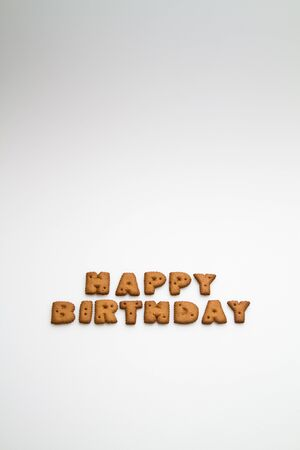 the words Happy Birthday made by brown biscuits on white surface in portrait orientation