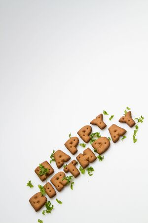 the words Happy Birthday made by brown biscuits and green leaves slanting on lower side of white surface in portrait orientation Stock Photo